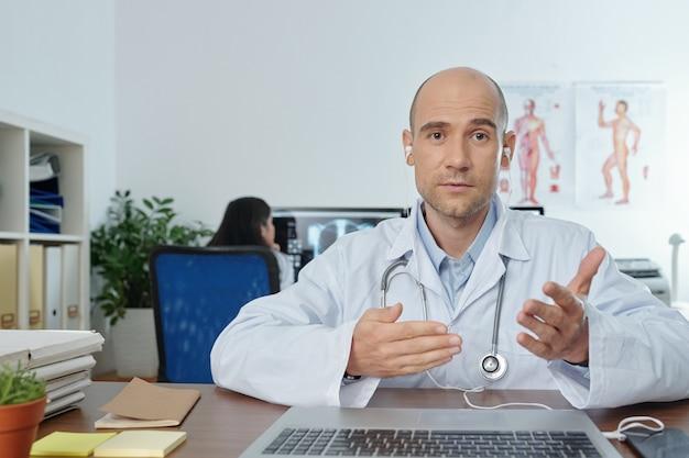 Medico di medicina generale che guarda la telecamera, gesticola e spiega nuovi metodi per trattare la polmonite batterica, il suo collega controlla i raggi x del paziente in background