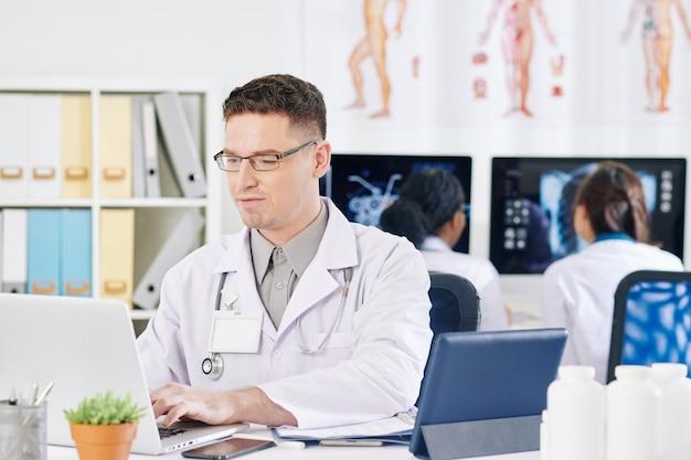 Medico di base che lavora al computer portatile