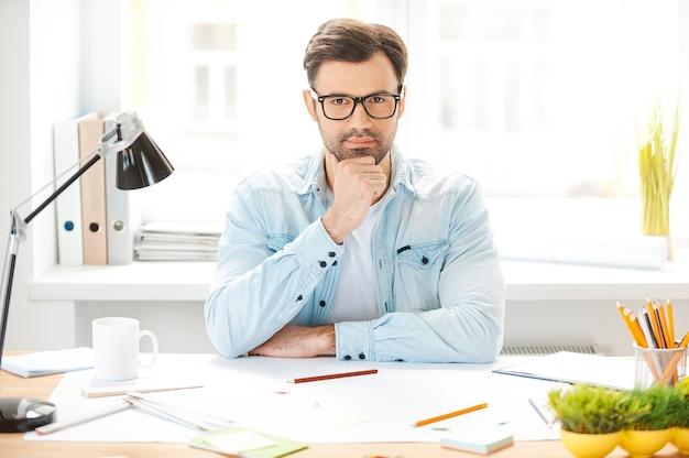 Generazione di nuove idee. bel giovane in camicia e occhiali che tiene la mano sul mento e guarda la telecamera mentre è seduto al suo posto di lavoro