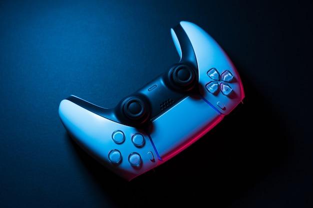 Controller di gioco bianco di nuova generazione isolato su sfondo nero con luci colorate che lo illuminano. avvicinamento. messa a fuoco selettiva.