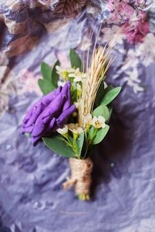 La porpora di boutonniere del fiore dello sposo delicato si trova su un fondo leggero del mestiere