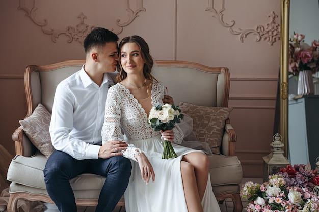 Dolce ritratto della sposa e dello sposo in un abito da sposa in pizzo in stile boho. sessione fotografica di matrimonio