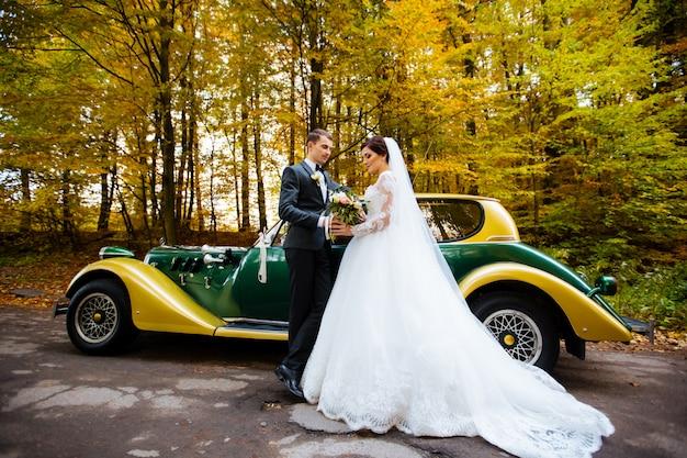Sposo e sposa alla moda delicati sull'automobile antiquata del fondo