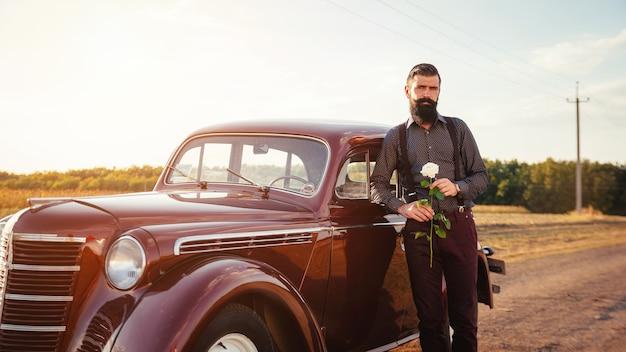 Gentiluomo bruna barbuto in una camicia, pantaloni con bretelle tiene una rosa bianca in mano vicino a un'auto retrò marrone su una strada di campagna e guarda l'orologio