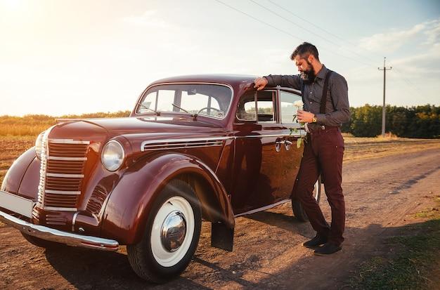 Signore con la barba in una camicia, pantaloni con bretelle tiene una rosa bianca in mano vicino a un'auto retrò marrone su una strada di campagna e guarda l'orologio