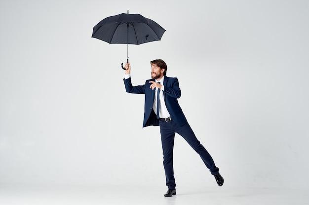 Un signore con un ombrello aperto in abito scuro piegato di lato