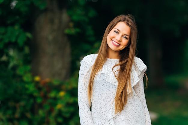 Sorriso genuino della ragazza che si è vestita con abiti bianchi e guarda l'obiettivo della fotocamera