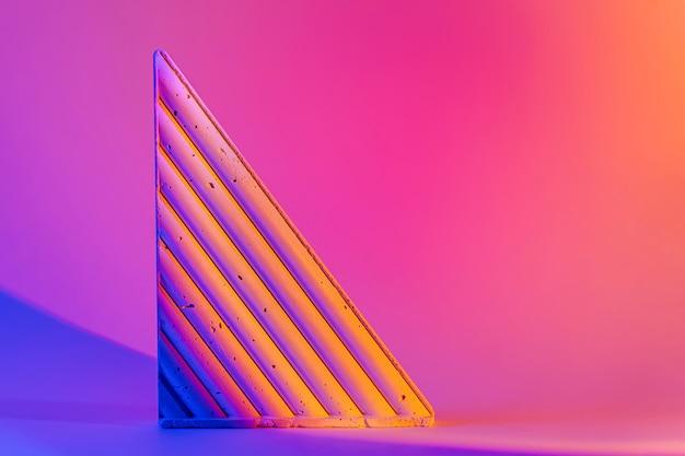 Figura geometrica concreta su sfondo al neon luminoso. forme geometriche alla moda.