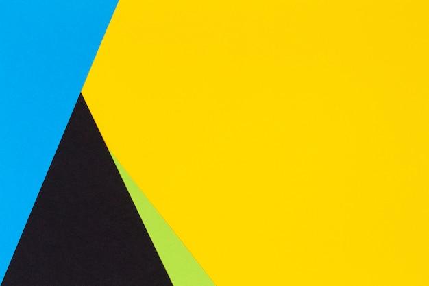 Parete di carta di colore giallo verde blu e nero a laici piatti geometrici