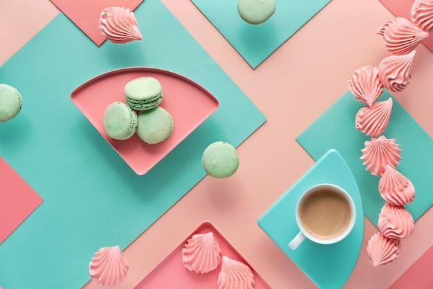 Sfondo di carta geometrica nei colori di menta e corallo con caffè e dolci