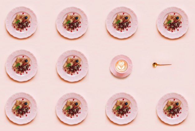 Motivo geometrico con frittelle sul piatto rosa e tazza di caffè su sfondo rosa.