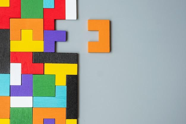 Blocco di forma geometrica con pezzo di puzzle in legno colorato.