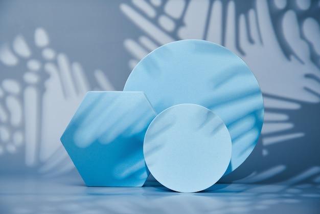 Forme geometriche su una parete blu, podi vuoti per la presentazione di vari prodotti, parete geometrica astratta con piedistallo