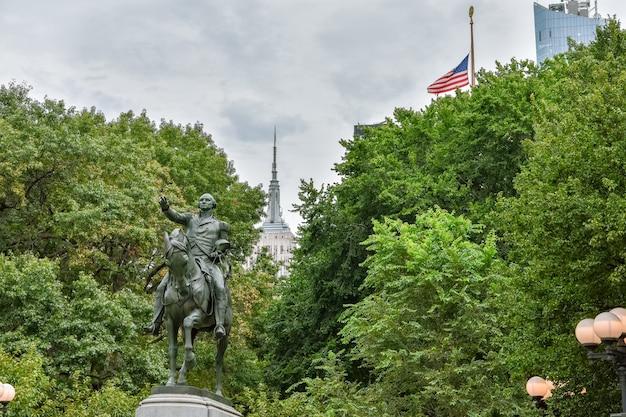 Statua di george washington a union square park. empire state e bandiera degli stati uniti in background. new york city, stati uniti.