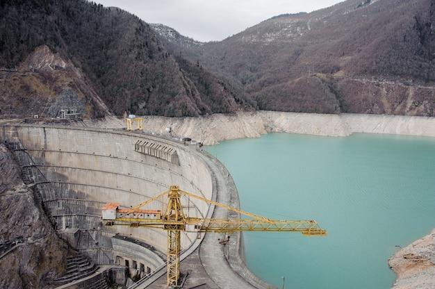 Georgia, svaneti, mestia. vista dall'alto sulla diga di enguri sulle montagne in primo piano della gru da cantiere gialla
