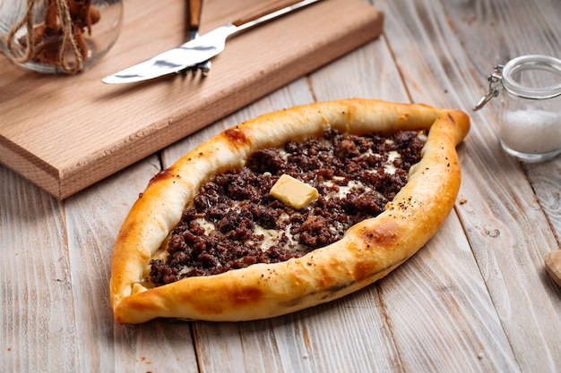 Khachapuri adjarian georgiano ripieno di carne macinata sul tavolo di legno