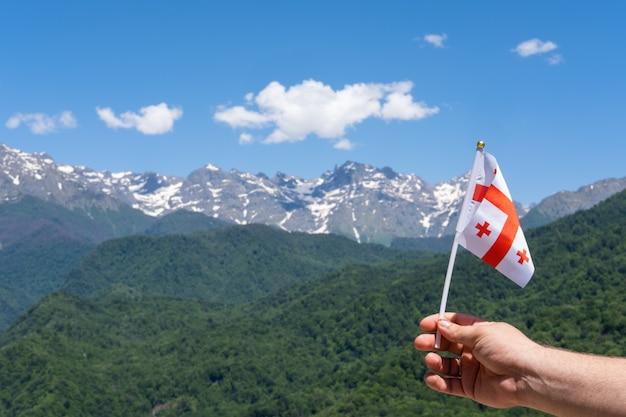 Bandiera georgiana in mano dell'uomo sullo sfondo delle montagne e del cielo blu