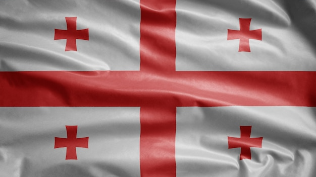 Bandiera georgiana che sventola nel vento. primo piano della bandiera della georgia che soffia, seta morbida e liscia. fondo del guardiamarina di struttura del tessuto del panno.