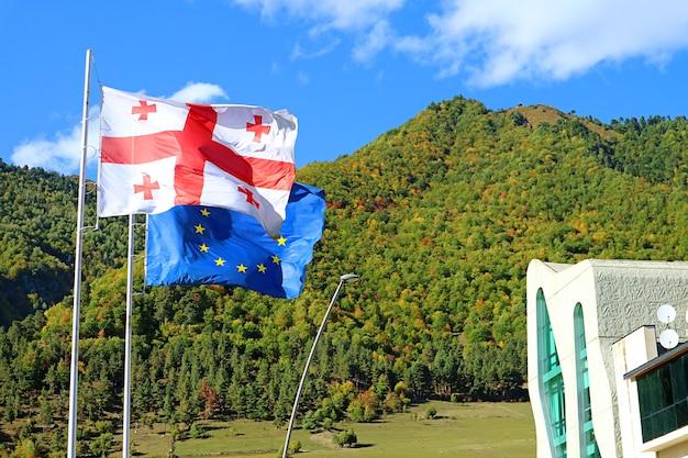 Bandiera georgiana con bandiera dell'ue sventola contro le prime colline autunnali della città di mestia svaneti regione georgia