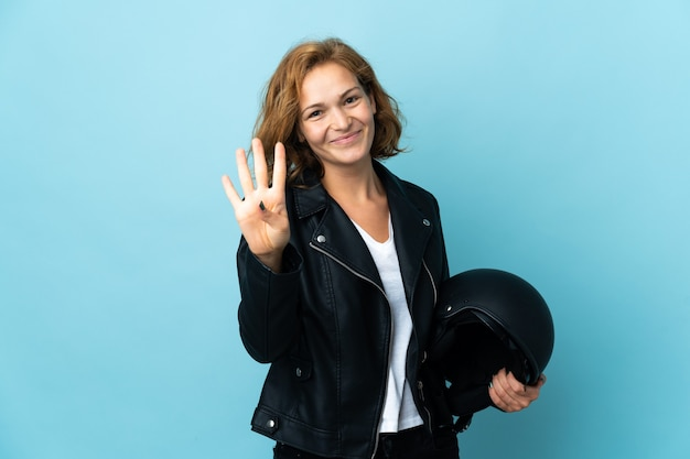 Ragazza georgiana che tiene un casco del motociclo isolato sulla parete blu felice e contando quattro con le dita