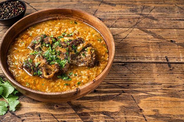 Zuppa di carne di agnello georgiana kharcho con riso, pomodori e spezie in una ciotola di legno