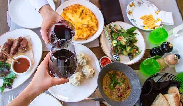 Il cibo del ristorante georgiano sul vino da tavola nelle mani
