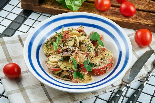 Insalata di verdure georgiana con pomodori, cetrioli e cipolle conditi con salsa di noci in una ciotola bianca. insalata in una composizione con ingredienti. avvicinamento. cibo piatto.