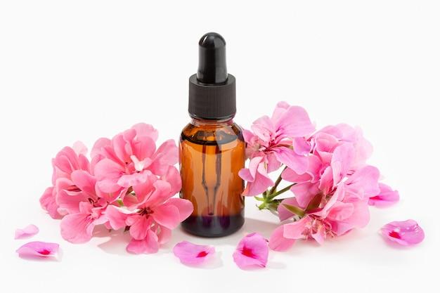 Olio essenziale del geranio sulla bottiglia ambrata isolata su fondo bianco. olio alle erbe