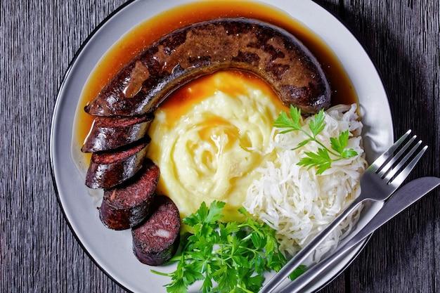 Cibo tedesco: blutwurst o sanguinaccio servito su un piatto con crauti, purè di patate prezzemolo, senape e grani di pepe su un tavolo di legno scuro, vista dall'alto, primo piano