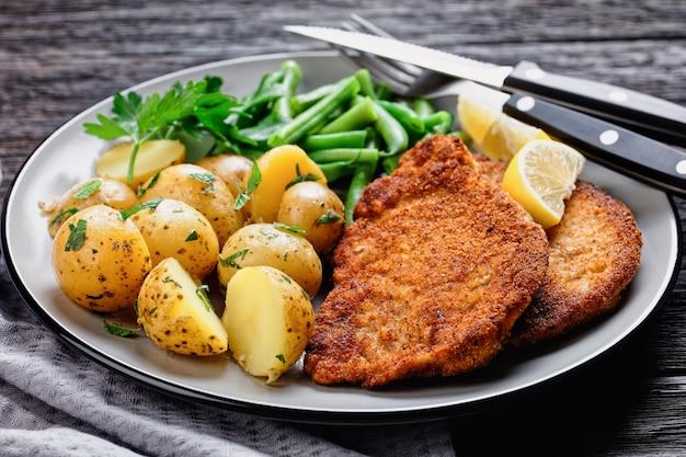 Cotoletta di maiale tedesca con patate novelle, fagiolini con posate serviti su un piatto con spicchi di limone e salsa a base di maionese su una superficie di legno scuro, vista dall'alto, primo piano