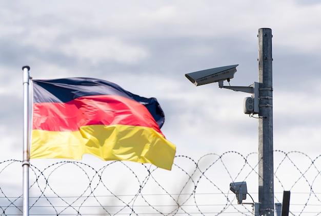 Confine della germania, ambasciata, telecamera di sorveglianza, filo spinato e bandiera della germania, immagine concettuale