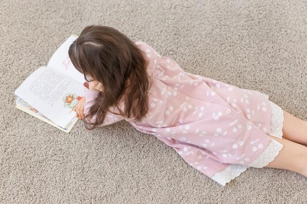 Gesign, bambino, concetto di persone - giovane ragazza sdraiata sul pavimento e leggere un libro.