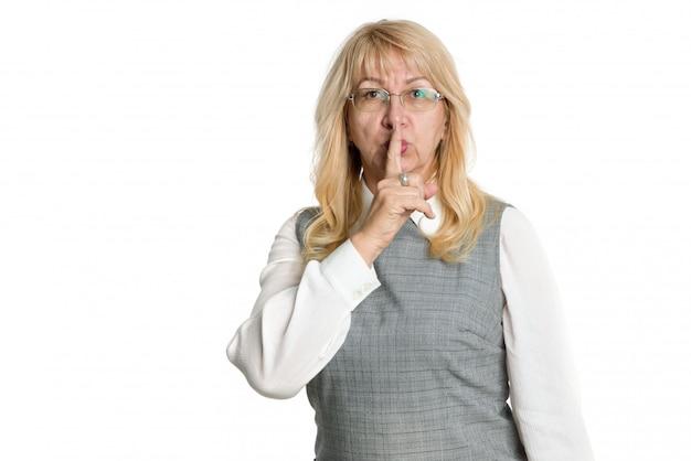 Il gesto è un segreto. una donna adulta con gli occhiali tiene un dito vicino alle labbra mentre si trova su uno sfondo chiaro.