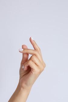 Gesto e segno, mano femminile su bianco. clic della mano o schiocco delle dita