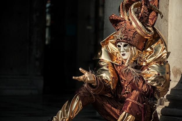 Gesticolando persona in costume di carnevale veneziano di arlecchino