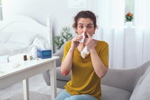 Guarisci presto. giovane signora dall'aspetto malato che si sente infelice sperando di riprendersi presto mentre cerca di decongestionare il naso