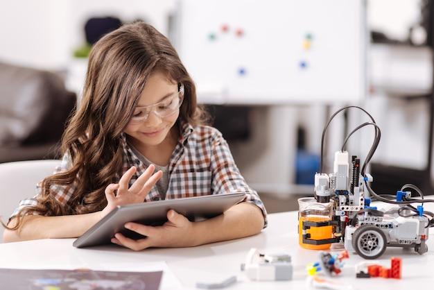 Acquisire nuove conoscenze. ragazza intelligente coinvolta sorridente che si siede nell'aula di scienze e utilizza il tablet durante la navigazione in internet