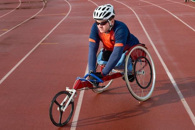 Prepararsi per la maratona. sportivo paraplegico professionista in sedia a rotelle da corsa in fase di riscaldamento prima della competizione allo stadio di atletica leggera