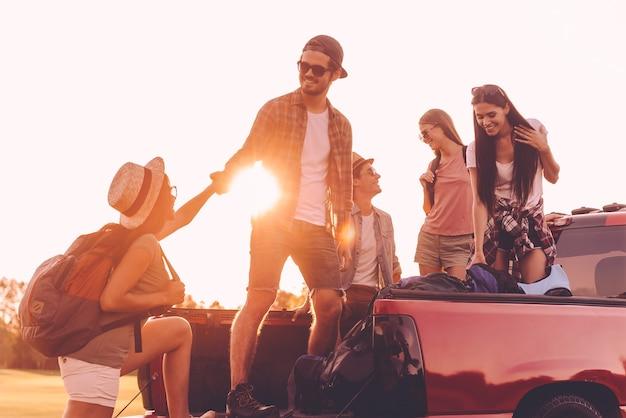 Prepararsi al viaggio su strada. bellissimi giovani che si preparano al viaggio mentre un uomo allegro aiuta la donna a raggiungere il pick-up