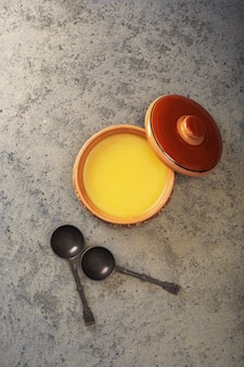 Olio di ghee in una pentola di ceramica sul tavolo. vista dall'alto.
