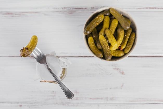 Cetrioli sottaceto cetrioli su una forchetta ciotola di verdure marinate su uno sfondo di legno bianco