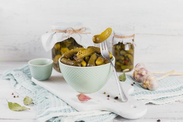 Cetriolini, cetrioli sottaceto su una forchetta, ciotola di verdure marinate su una superficie di legno bianca. mangiare pulito, concetto di cibo vegetariano