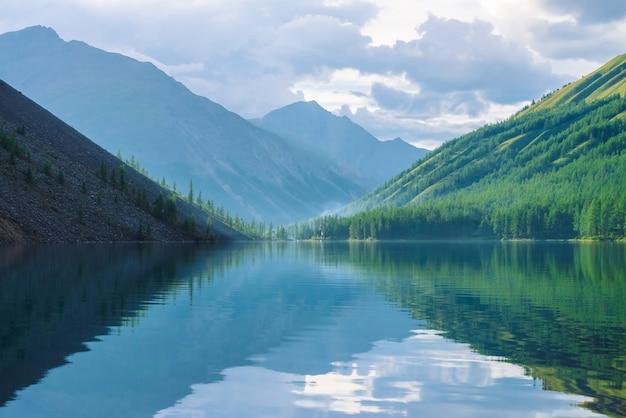 Lago spettrale della montagna in altopiani al primo mattino. belle montagne nebbiose si riflettono nella calma superficie dell'acqua chiara. fumo di fuochi. incredibile paesaggio nebbioso d'atmosfera di natura maestosa.