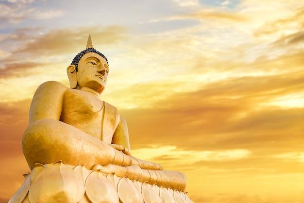 Il gigantesco buddha d'oro. la grande statua del buddha con sfondo tramonto o alba. statua del buddha seduto. credere, cultura, tradizionale. il buddista crede il concetto. concetto di meditazione calma. copia spazio.