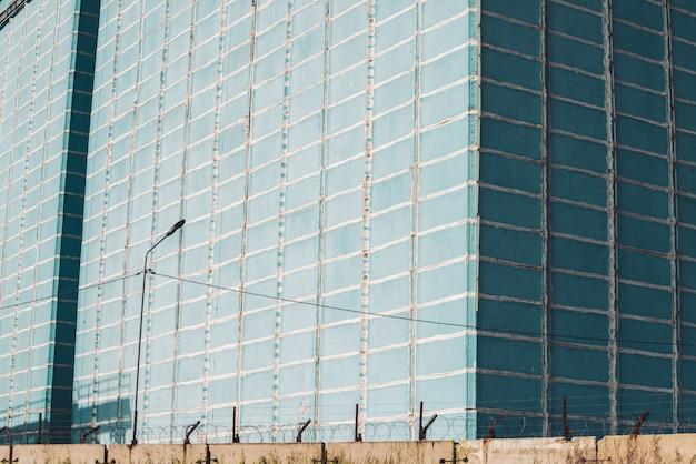 Edificio di produzione multipiano gigante dietro recinzione con filo spinato. pittoresca vecchia fabbrica funzionante rinnovata. oggetto industriale. grattacielo di produzione di grandi dimensioni. primo piano della zona industriale.