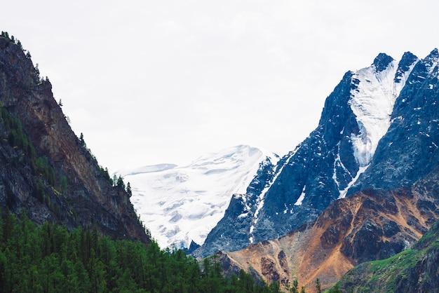 Cima innevata gigante della montagna nell'ambito della fine del cielo nuvoloso su