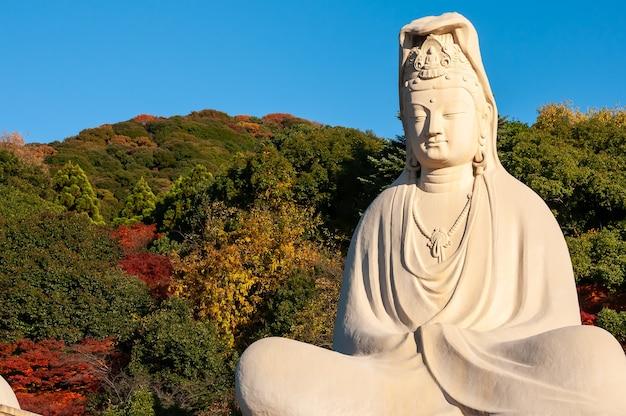 Statua gigante di ryozen kannon bodhisattva avalokitesvara, illuminata da un'incredibile luce solare, montagne autunnali, cielo blu.