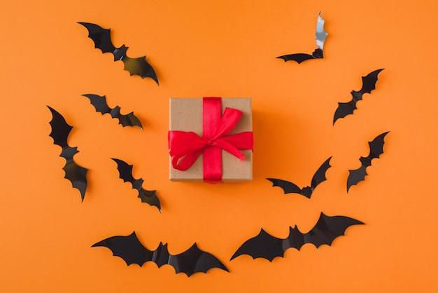 Regalo sullo sfondo di pipistrelli su sfondo arancione. copia spazio.