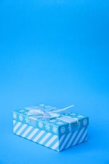 Regalo una confezione regalo blu con un fiocco è isolata su uno sfondo blu un biglietto di capodanno natale