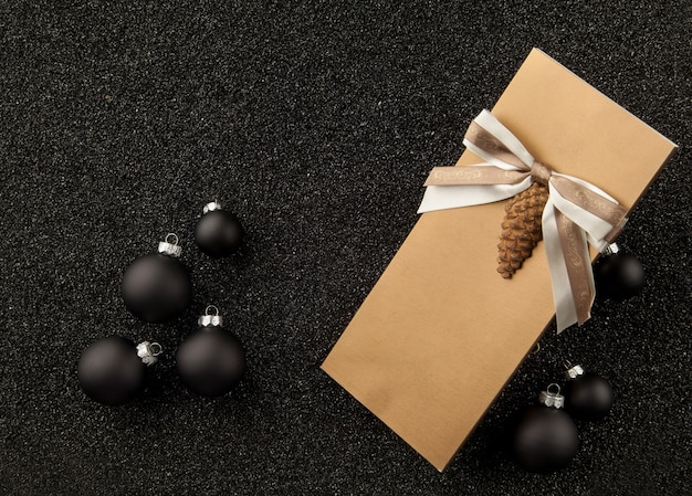 Libretto regalo con decorazioni per l'albero di natale su sfondo nero granuloso